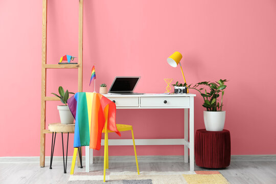 Modern workplace with flag of LGBT hanging on chair