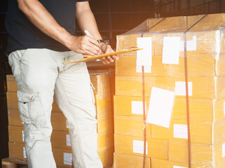 Warehouse worker holding clipboard doing inventory management package boxes. check stock. shipment boxes.