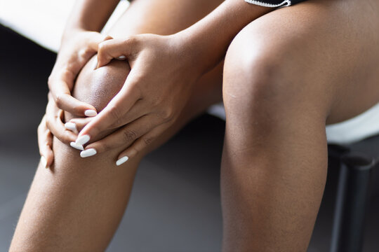 Black African young woman having knee joint pain or knee injury problem, concept of knee joint surgery or orthopedics treatment