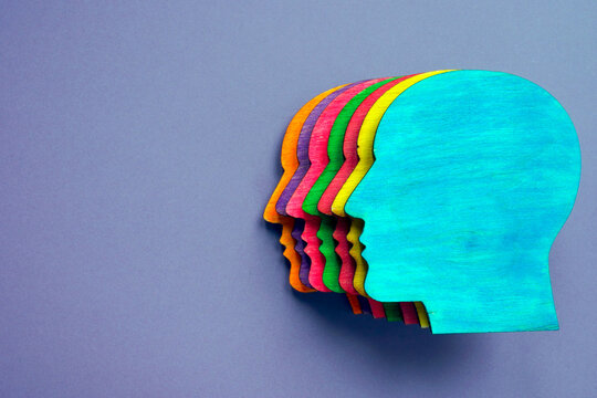 Wooden head with different colors as symbol of diversity and inclusion.