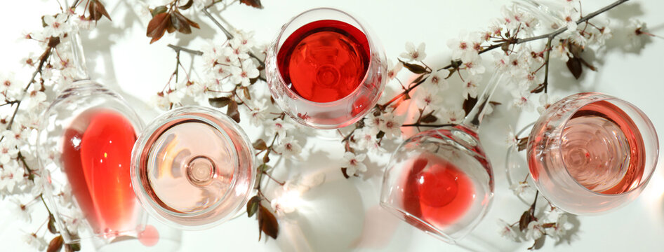 Glasses of wine and cherry flowers on white background