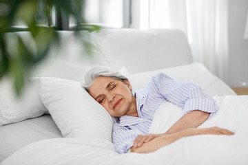Obraz old age and people concept - senior woman sleeping in bed at home bedroom - fototapety do salonu