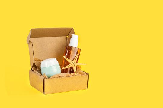 Potes de cremas para la cara y el cuerpo junto a una caja de cartón sobre un fondo amarillo liso y aislado. Vista de frente. Copy space