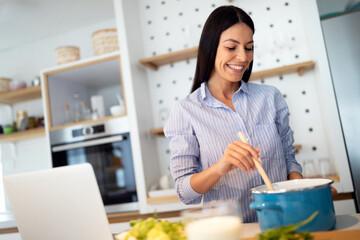 Fototapeta Happy woman in kitchen following recipe on digital device during cooking. obraz
