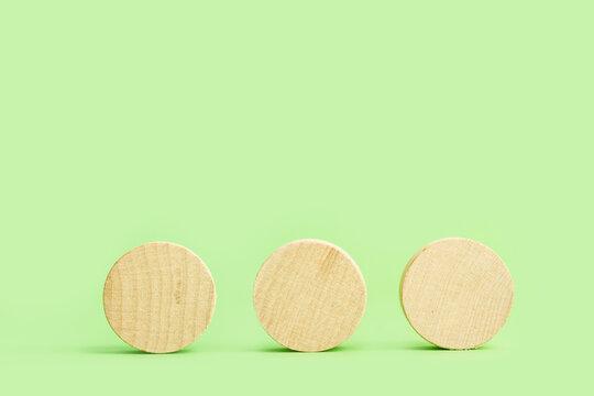 Tres circulos de madera sobre un fondo verde claro liso y aislado. Vista de frente. Copy space