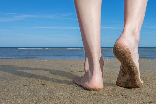close-up ankle Jambes de la femme et de pieds marchant sur le sable de la plage avec l'eau de mer en arrière-plan