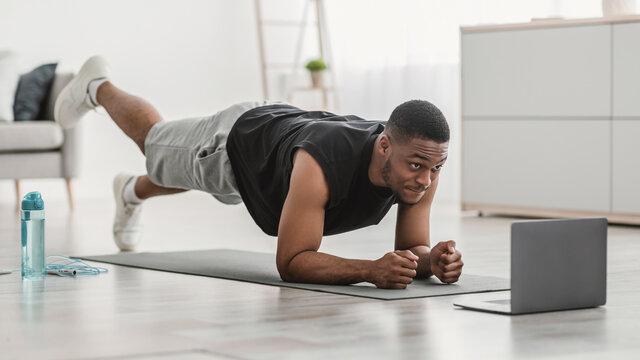 Man At Laptop Standing In Plank Doing Leg Raise Indoor