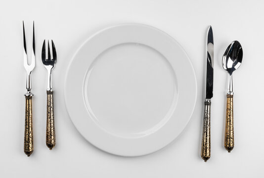 Empty plate with cutlery isolated on white background