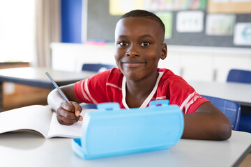 Fototapeta Portrait of african american boy smiling while sitting on his desk in the class at school obraz