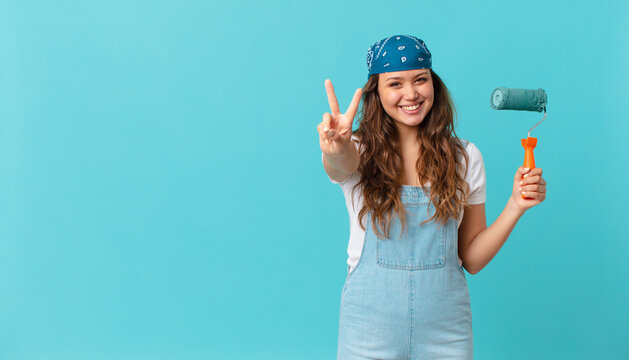 young pretty woman smiling and looking happy, gesturing victory or peace and painting a wall
