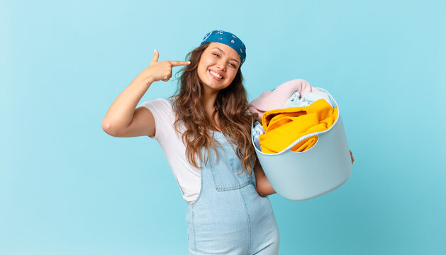 young pretty woman smiling confidently pointing to own broad smile and holding a wash clothes basket
