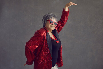 Fototapeta Side view of happy confident beautiful youthful senior woman in red sequin jacket dancing on gray studio background. Crazy retired old grandma having fun and doing funny egyptian arm dance move obraz