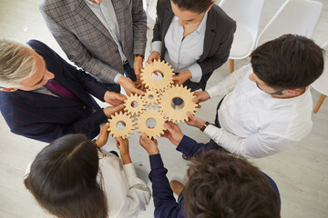 Obraz Team of business people connect cogwheels as metaphor for good teamwork and work efficiency, high angle, from above. Senior and young entrepreneurs form an alliance and organize parts into one system - fototapety do salonu