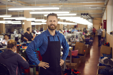 shoemaker. Portrait of a confident smiling factory worker or shoe factory owner at work. Caucasian handsome bearded man in a black work apron holds his hands to his sides looking at the camera. - fototapety na wymiar