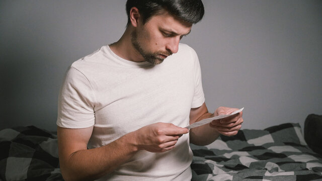 Man reading drug label to check that before or after meal in evening at home at bedroom sitting on bed. Concentrated male reviewing instruction medications. Guy reading flyer before taking medicine