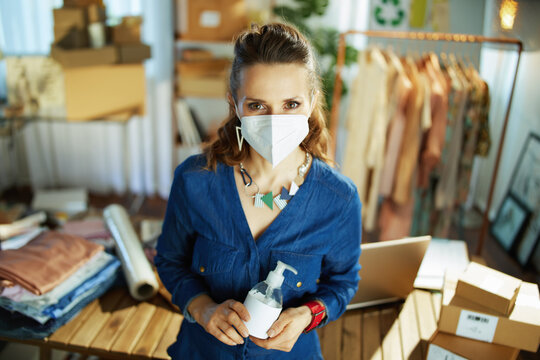 young small business owner woman with ffp2 mask in office