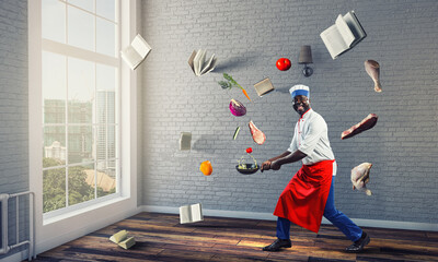 Black man wearing an apron and cooking in action. Mixed media - fototapety na wymiar