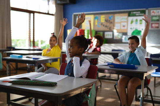Group of diverse students raising their hands in the class at elementary school