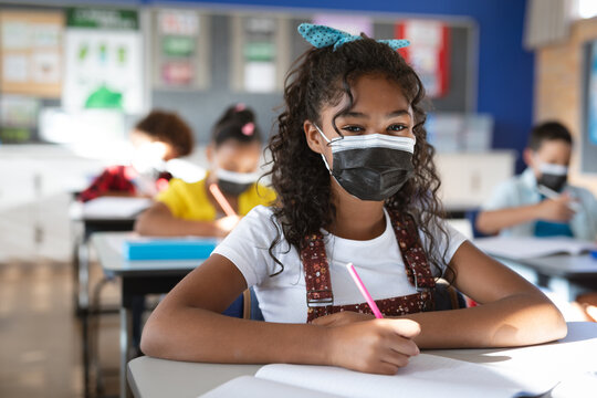 Portrait of african american girl wearing face mask sitting on her desk at elementary school
