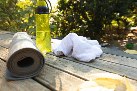View of rolled yoga mat, white towel and yellow water bottle on terrace