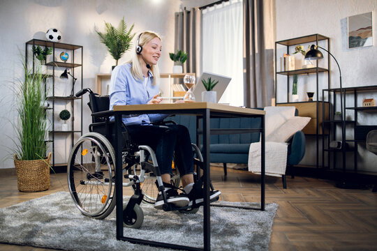 Pretty young woman in wheelchair using headset and laptop for video conference at home. Handicapped business lady leading working meeting online.