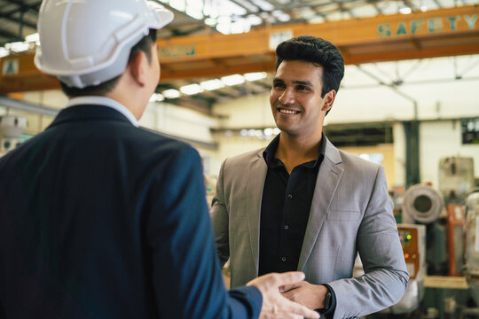 30s young Asian businessman in formal suit and hard hat showing foreign business partner in factory background. Business partnership and team work success concept