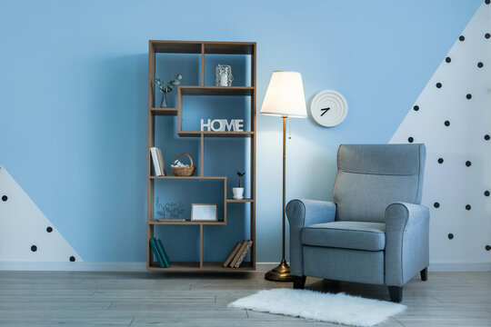 Glowing lamp with armchair and book shelf near color wall