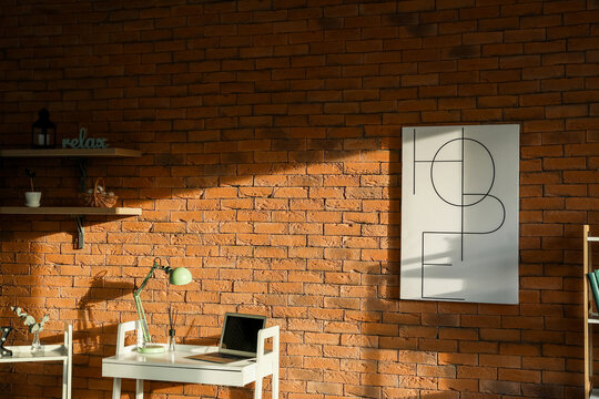 Modern workplace with laptop and lamp near brick wall