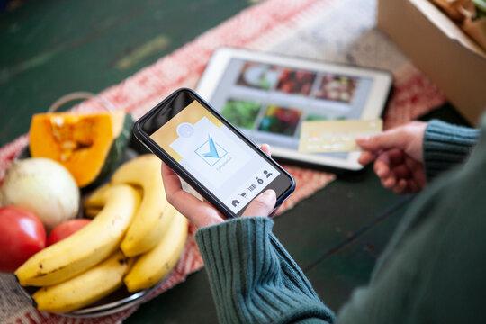 ネットスーパーの決済をスマートフォンで行う女性
