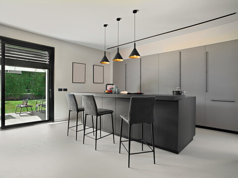 modern kitchen interior in the foregorund there is a island kitchen with stools