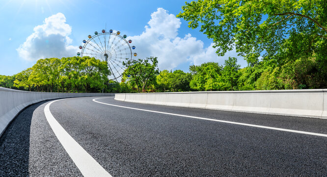 Empty asphalt road and ferris wheel with green forest under blue sky.