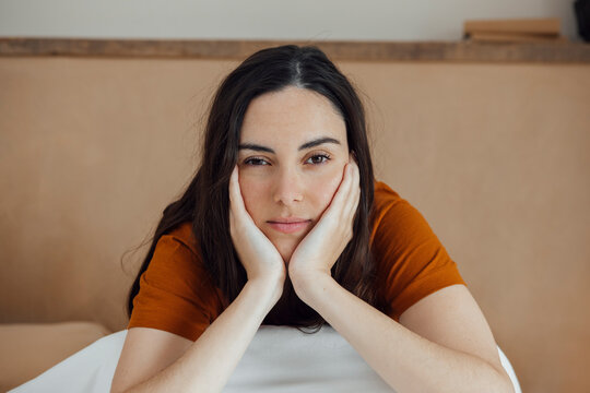 Dreamy woman sitting on comfortable bed in morning