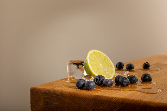 Ice cubes with lemon or lime, and blueberries on a nice textured oak table. the ice is melting on the table and creates a wet spot.