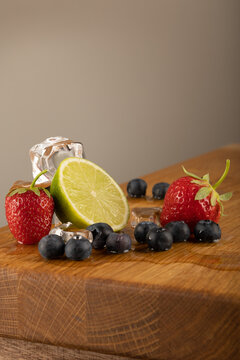 A collection of fruits with ice cubes on the sides. These contain home grown blueberries, strawberries and lime or lemon fruits, in melting ice scene. shot on an oak table surface.