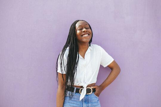 Smiling black woman standing near wall