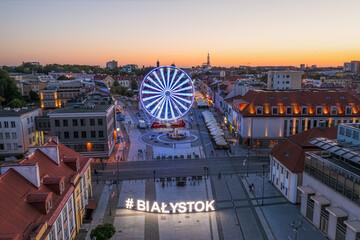 Obraz Białystok, widok z lotu ptaka o zmierzchu na Ratusz, Rynek Kościuszki, koło widokowe i napis #Białystok - fototapety do salonu