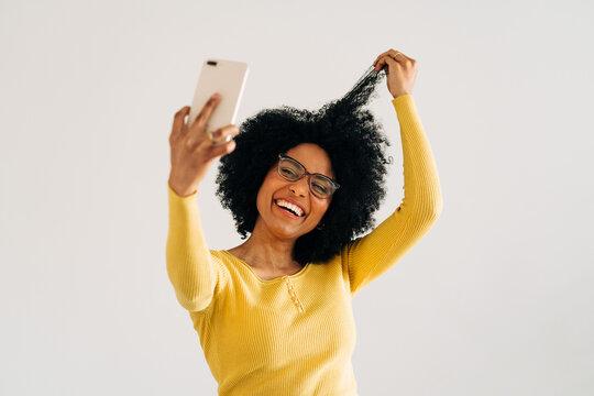 Happy black woman in eyeglasses smiling and taking selfie