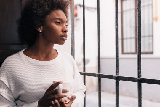 Pensive young African American female drinking coffee near grid fence in house