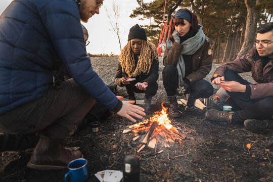 Cheerful diverse friends sitting around bonfire on river bank