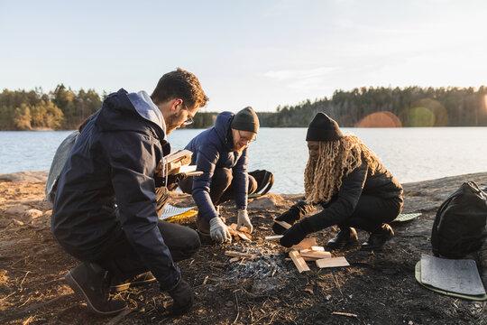 People in gloves preparing wood for bonfire