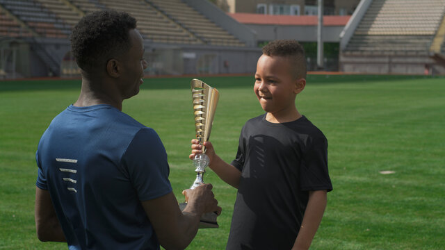 Black trainer giving cup to boy on football pitch