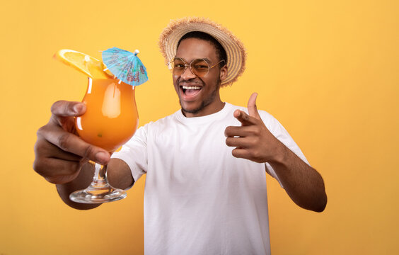 Carefree black guy in casual wear holding tropical cocktail and pointing at camera on yellow studio background