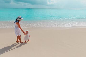 Fototapeta mother and little daughter walking on beach obraz