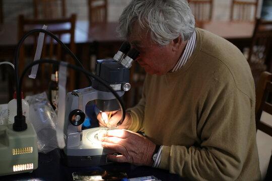 Austrian ecologist Fritz Schiemer looks through a microscope in Brataj
