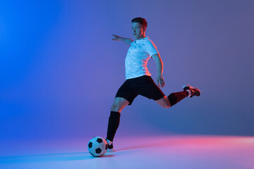 Obraz Young Caucasian man, male soccer football player training isolated on gradient blue pink background in neon light - fototapety do salonu