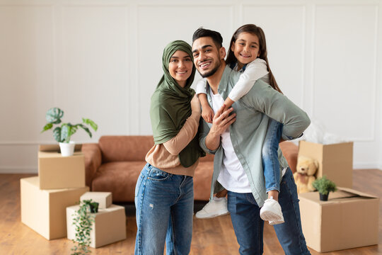 Happy muslim family looking at camera, posing on moving day