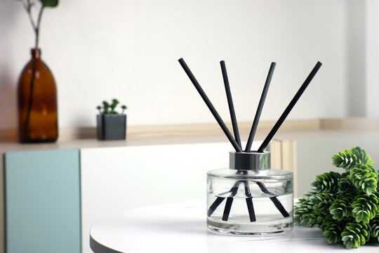 luxury aroma scented reed diffuser crystal bottle is used as room freshener and decoration items on white marble table in the nice modern living room to creat relax ambient in the evening