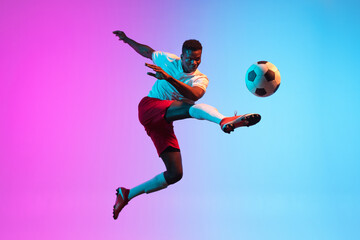 Obraz One African man, professional soccer football player training isolated on gradient blue pink background in neon light. - fototapety do salonu