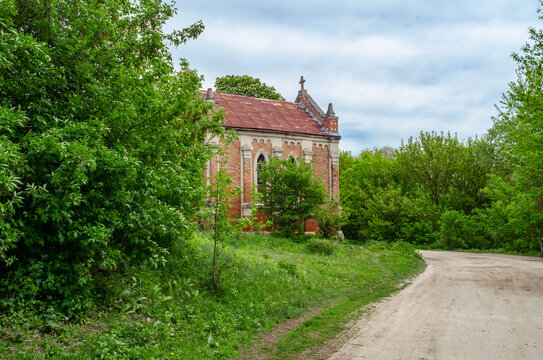 Old abandoned church with red bricks on a background of trees