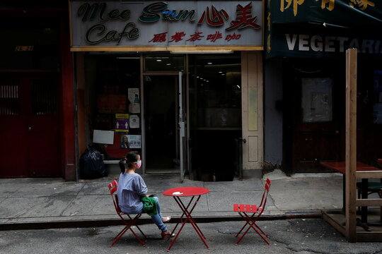 A woman sits alone wearing a protective face mask, following the May 31, 2021 unprovoked attack on a 55 year old Asian woman, outside a cafe in Manhattan's Chinatown district of New York City,